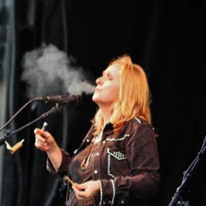 Melissa Ethridge smoking a marijuana joint and vape pen on stage.